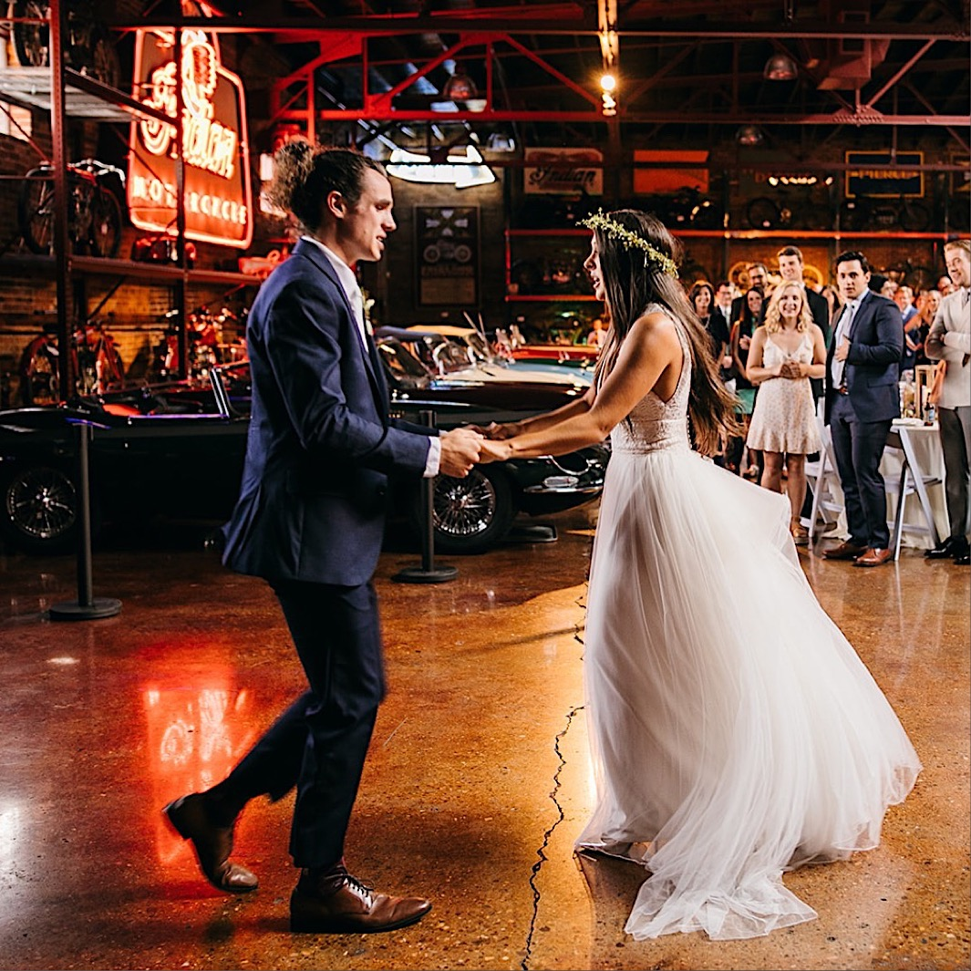 bride and groom dance near vintage cars and neon signs at their downtown Chattanooga wedding reception at The Coker Museum in Chattanooga
