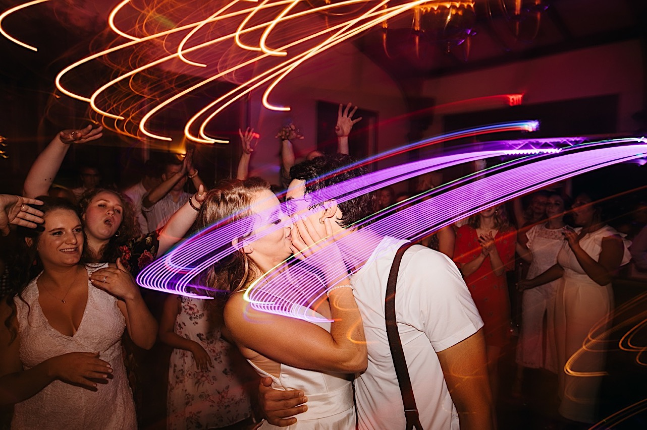 groom in white undershirt and suspenders kisses bride under dark reception lights while wedding guests cheer