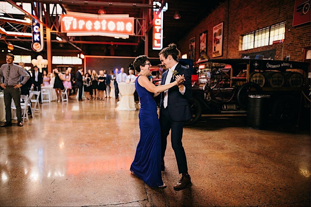groom dances with his mother near vintage truck under neon Firestone sign at The Coker Museum in Chattanooga Tennessee