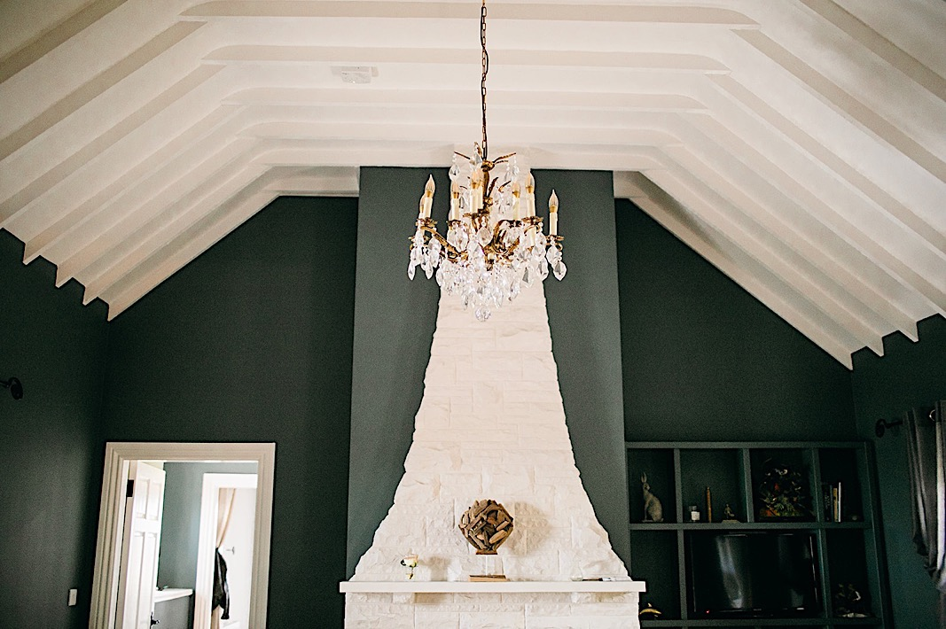 Gold chandelier hangs in a forest green room