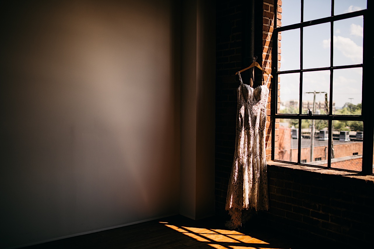 lacy wedding dress hangs from a wooden hanger in a large window at The Turnbull Building