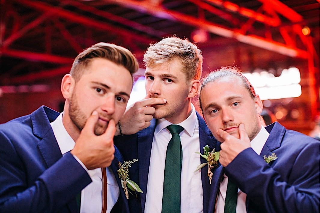 groomsmen in blue suits and green ties smooth their mustaches