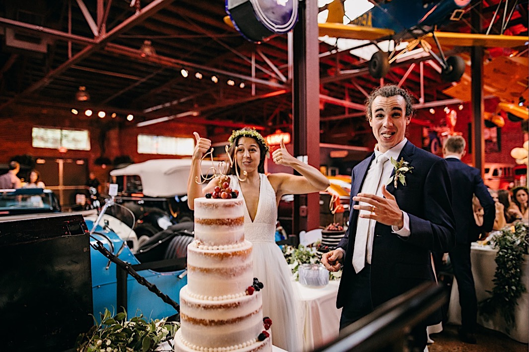 bride and groom give thumbs up to their naked wedding cake
