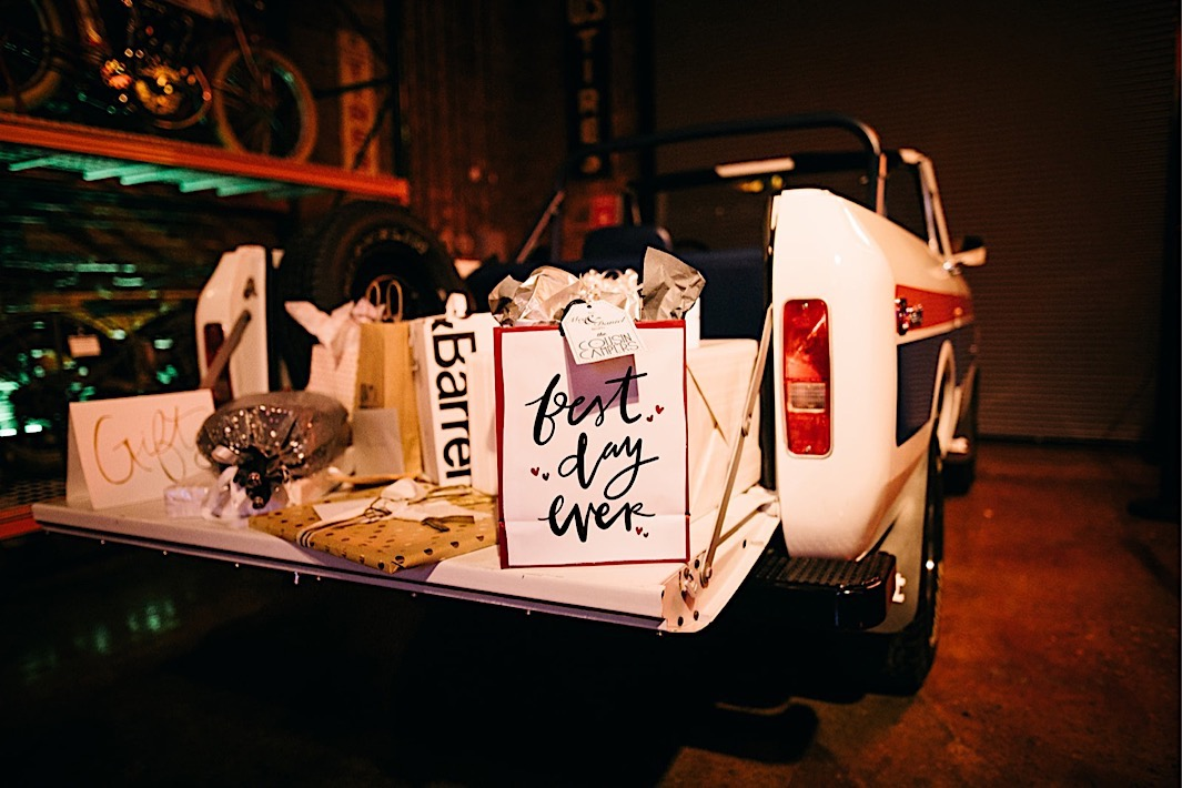 wedding gifts sit on the tailgate of a vintage pickup truck