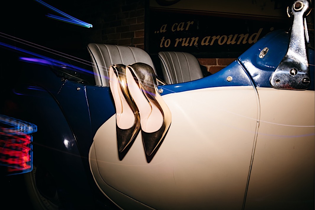 silver pump heels rest over the side of a vintage car at The Coker Museum in Chattanooga Tennessee