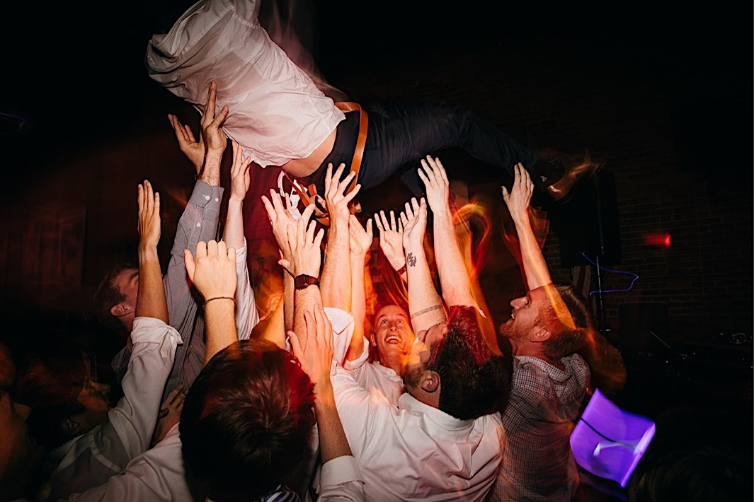 men toss groom into the air and hold their hands up to catch him