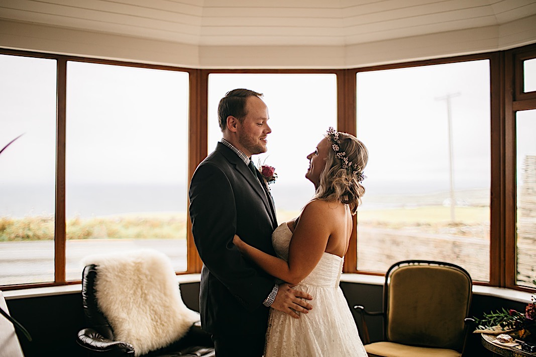 Bride and groom hold each other and smile during their first look at their elopement in the Moher Cliffs