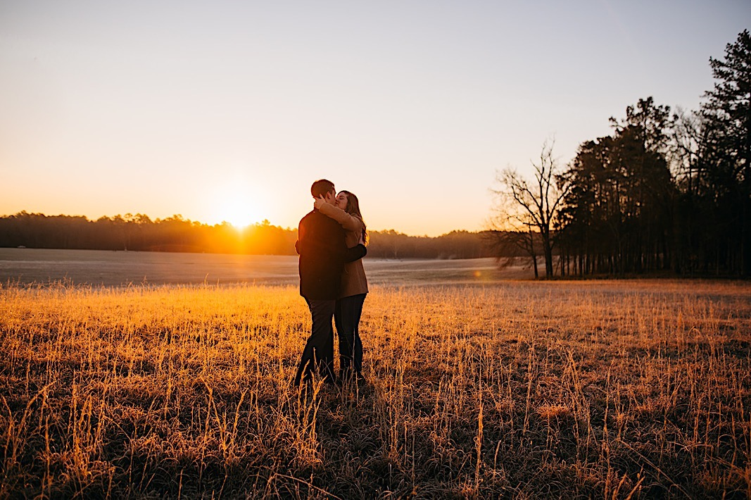 Couple embracing at sunset for their engagement photography session with Our Ampersand Photography