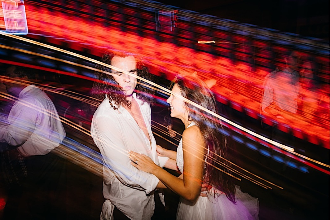 bride and groom dance under colored lights