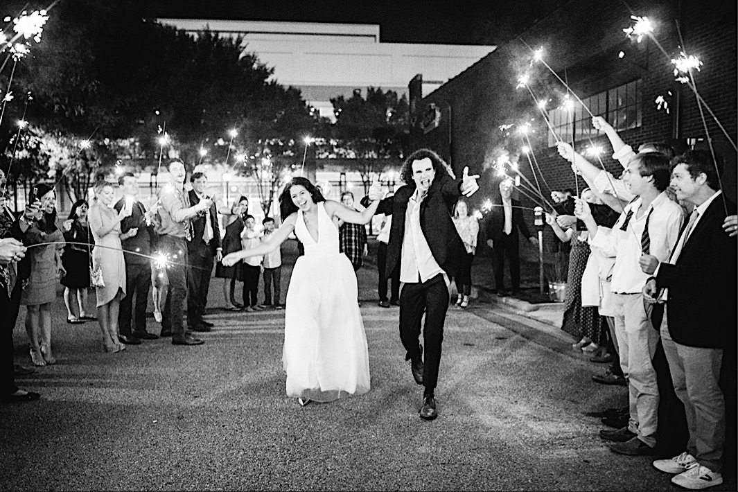 bride and groom laugh and walk between guests holding long sparklers overhead