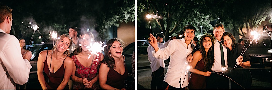wedding guests hold long sparklers and smile in the night