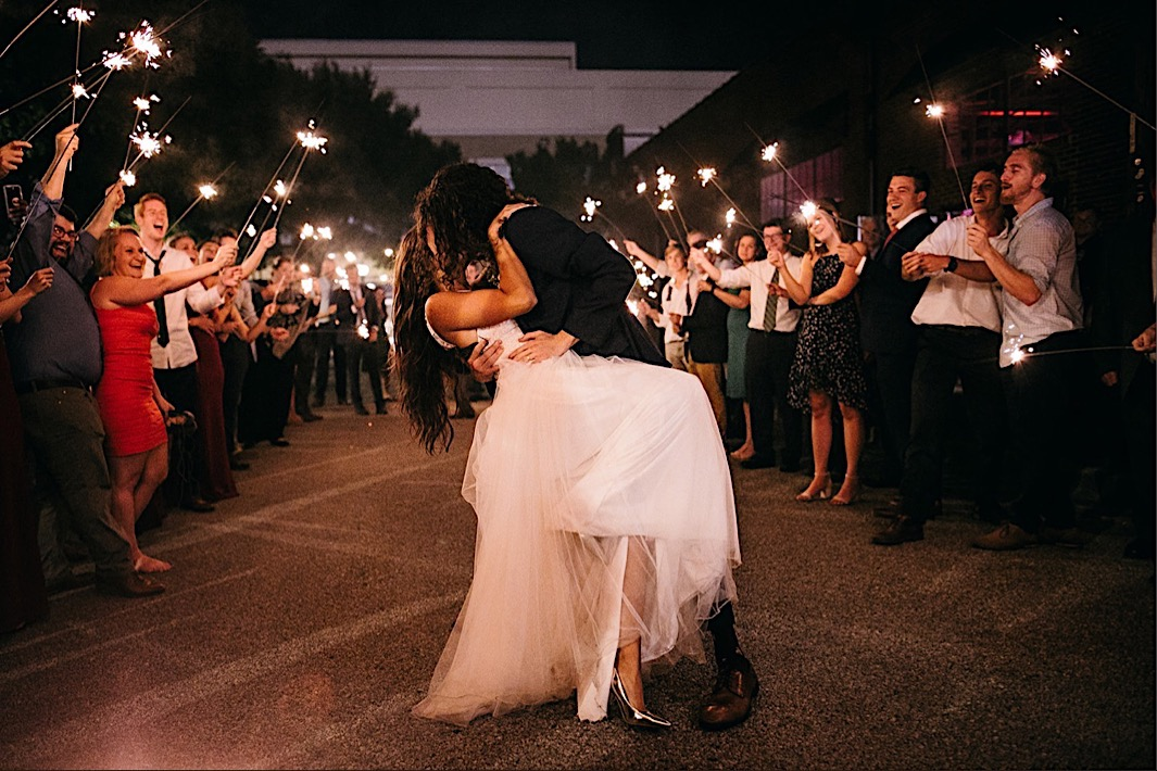groom dips bride for a kiss between wedding guests holding sparklers