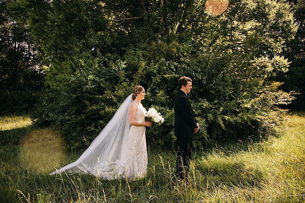 in a grassy field, bride wearing long veil and holding large bouquet of white flowers approaches groom with his back turned