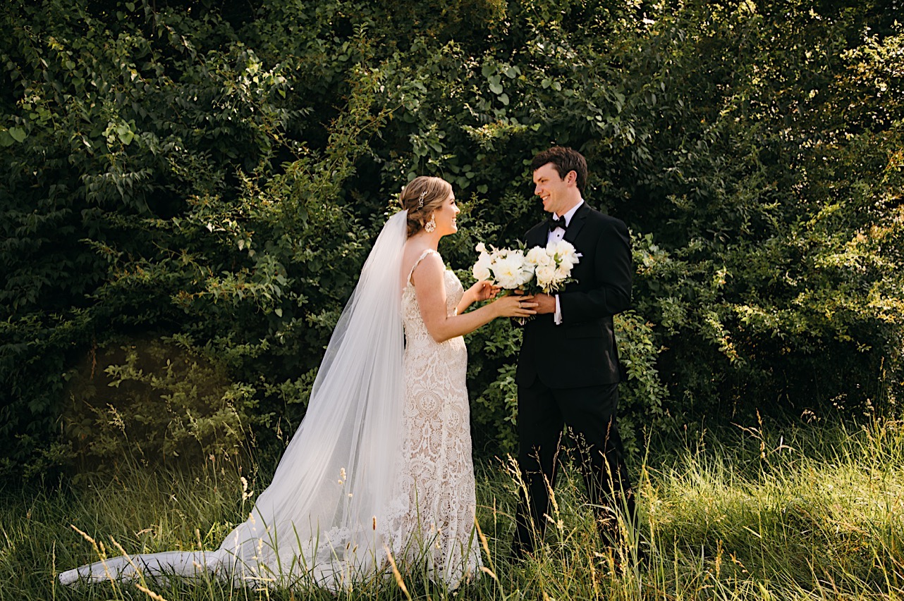 groom faces bride in a grassy field. he holds her large bouquet of white flowers