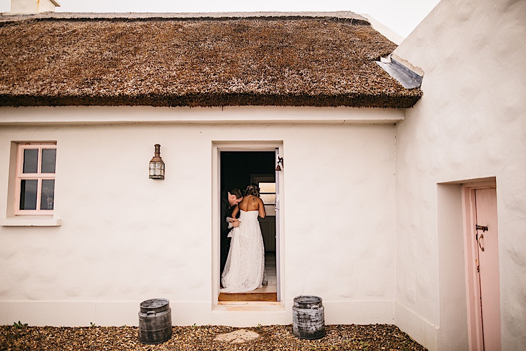 Bride stands in a doorway as groom fixes her dress before their elopement photos at the Moher Cliffs