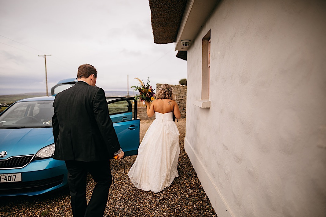 Bride and groom walk towards a blue bmw outside the Moher Cliffs