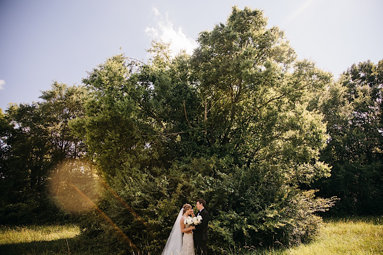 bride and groom stand facing each other in front of a large, overgrown tree and shrubbery
