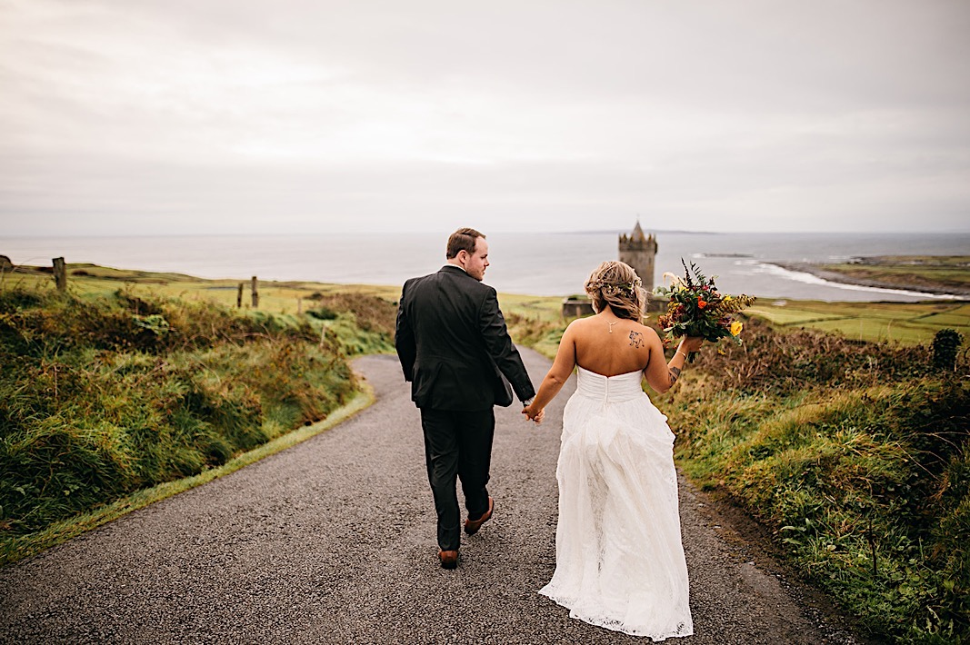 Bride and groom hold hands and walk down the street during their engagement photos at the Moher Cliffs