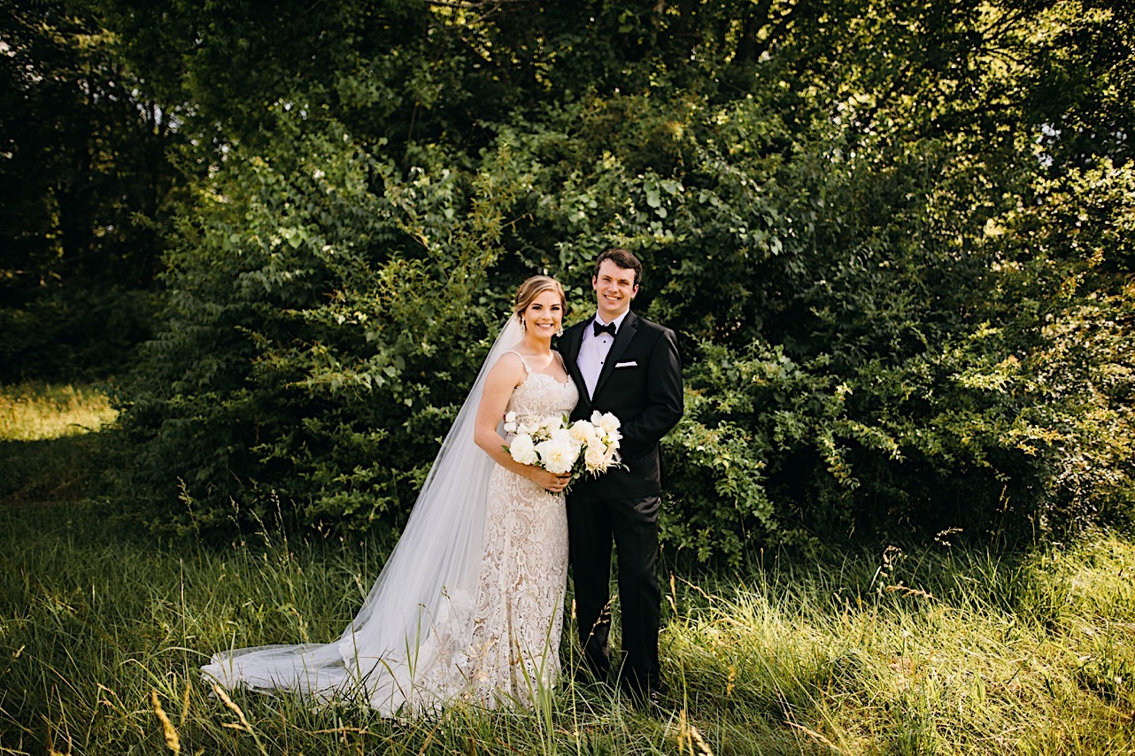 bride and groom stand in a grassy field. his arm is around her waist, and she holds a large Petaline bouquet of white flowers