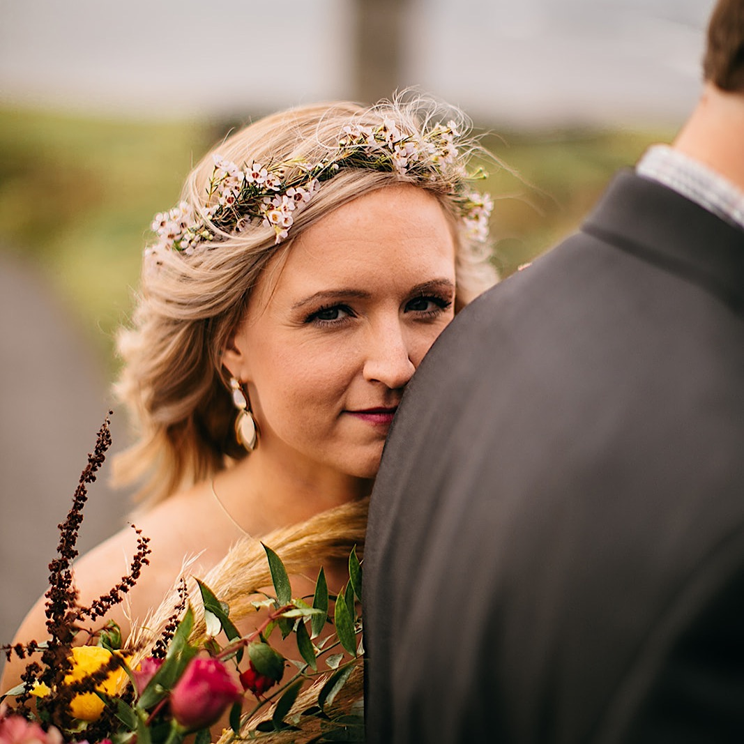 Bride leans her head against the groom while holding her bouquet and smiles for their elopement photos at the Moher Cliffs