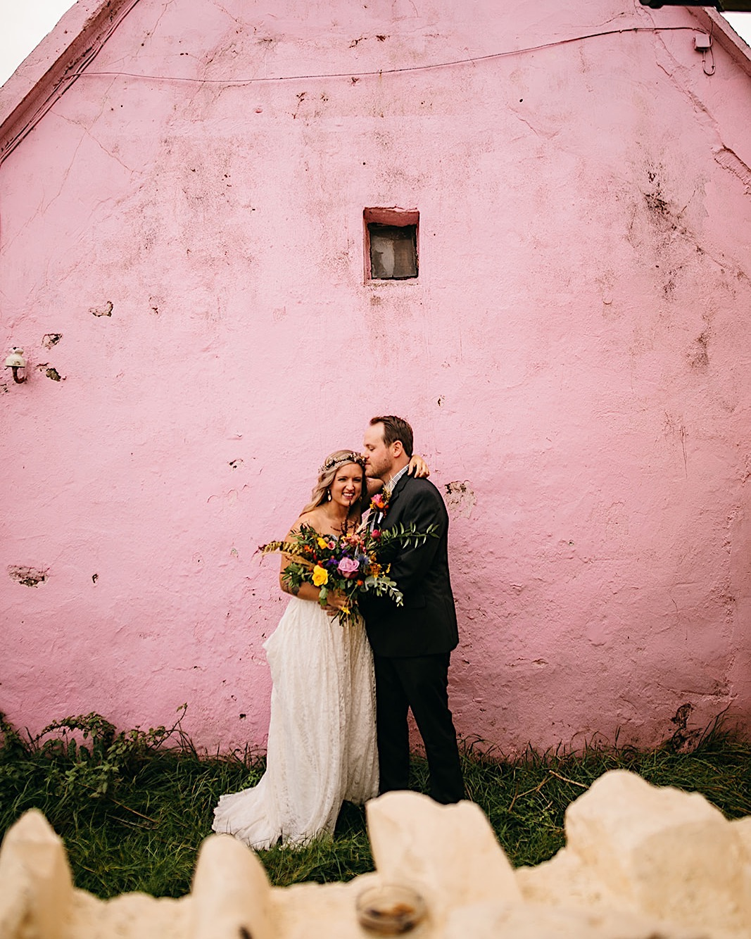 Bride and groom embrace and smile in front of a bubblegum pink wall.