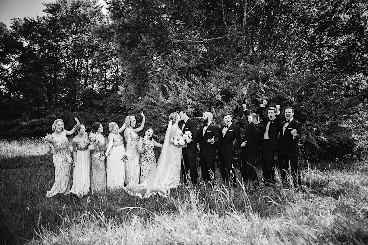 bride and groom kiss in a grassy field with their bridal party cheering on either side of them