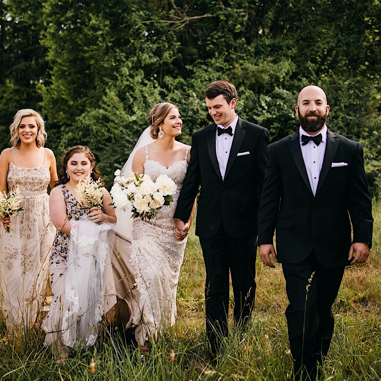 bride in lacy wedding gown smiles up a groom as they and their bridal party walk in a grassy field