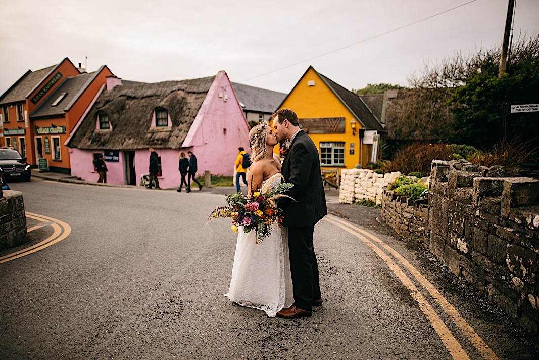 Bride and groom share a kiss in the road near the Moher Cliffs