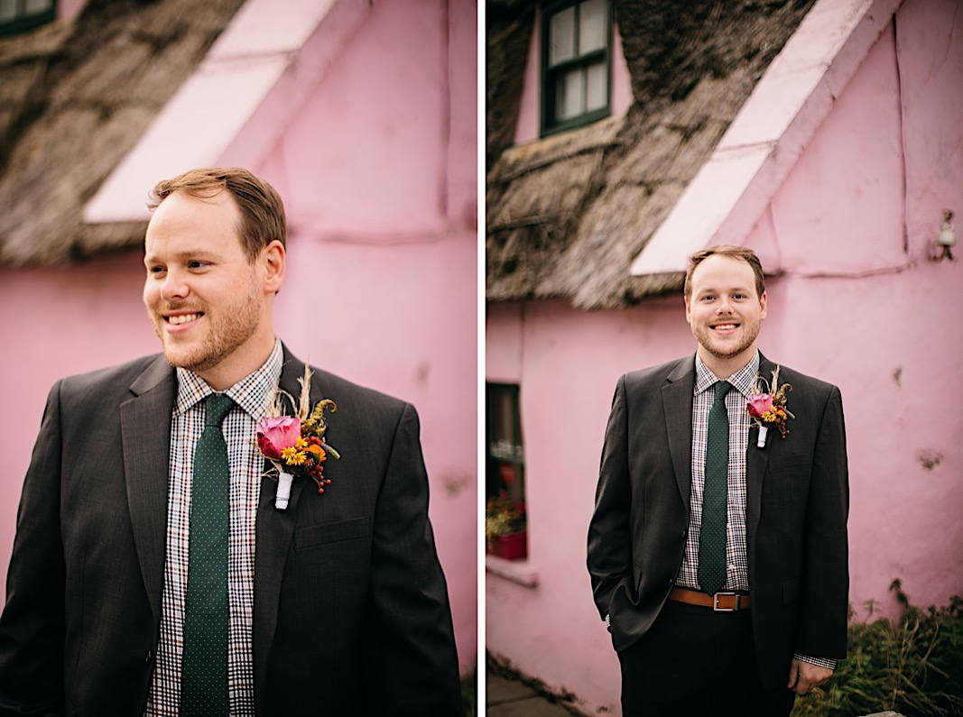 Groom poses and smiles in front of a pink house during his elopement photos at the Moher Cliffs