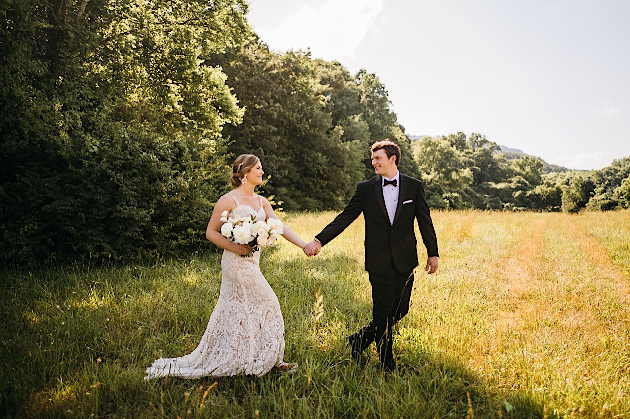 groom holds brides hand and they walk through a grassy field. she carries a large bouquet of white flowers