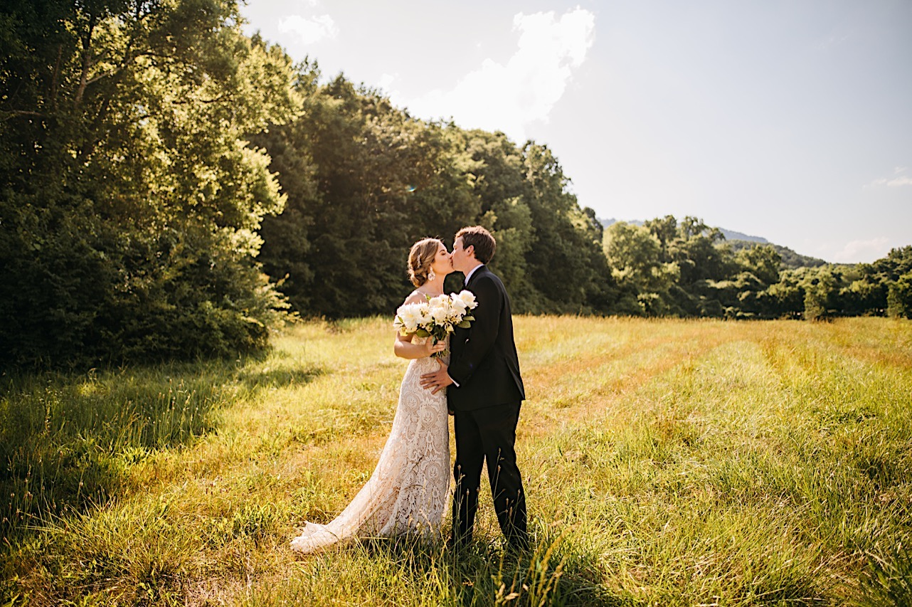 bride and groom kiss in a grassy field surrounded by tall trees. she holds a large Petaline bouquet of white flowers