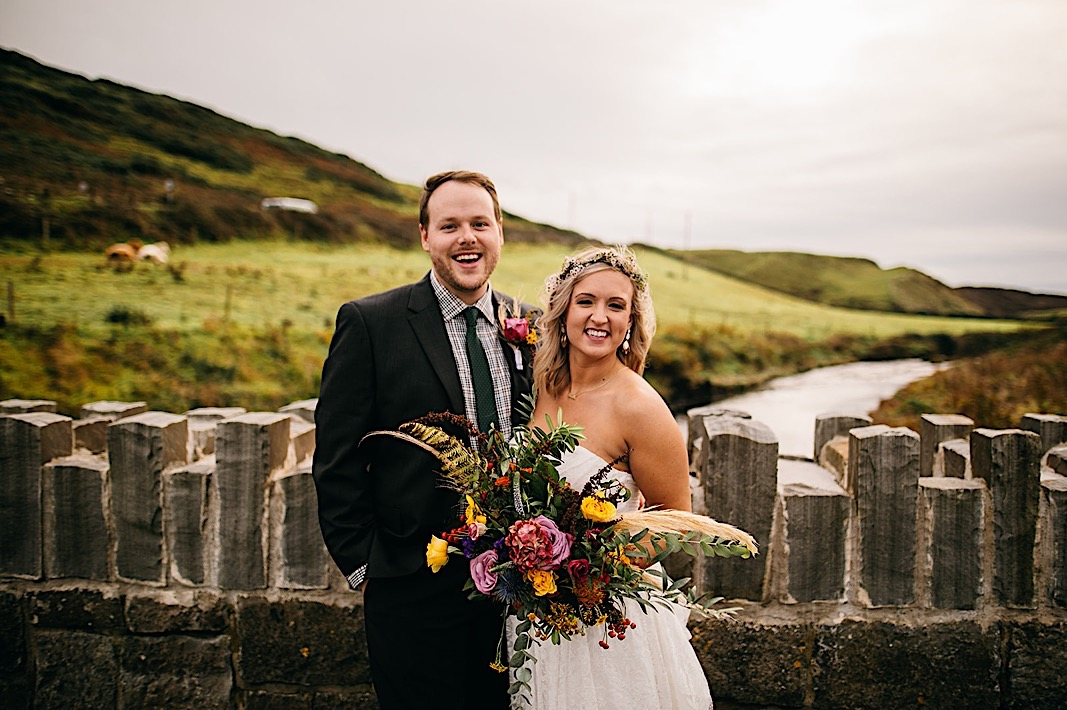 Bride and groom laugh on a bridge during their elopement photos at the Moher Cliffs