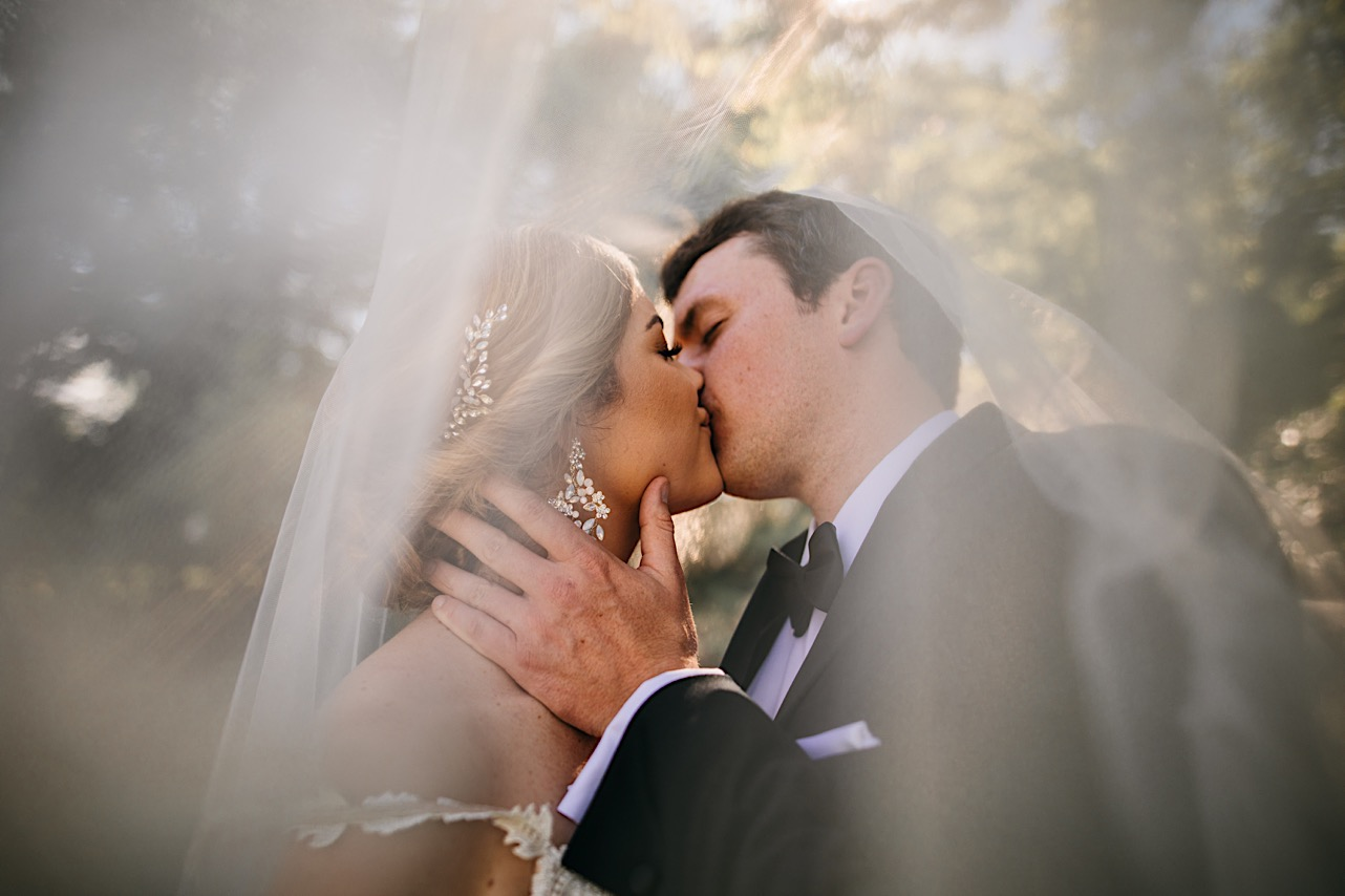 groom holds bride's face and kisses her under her sheer veil
