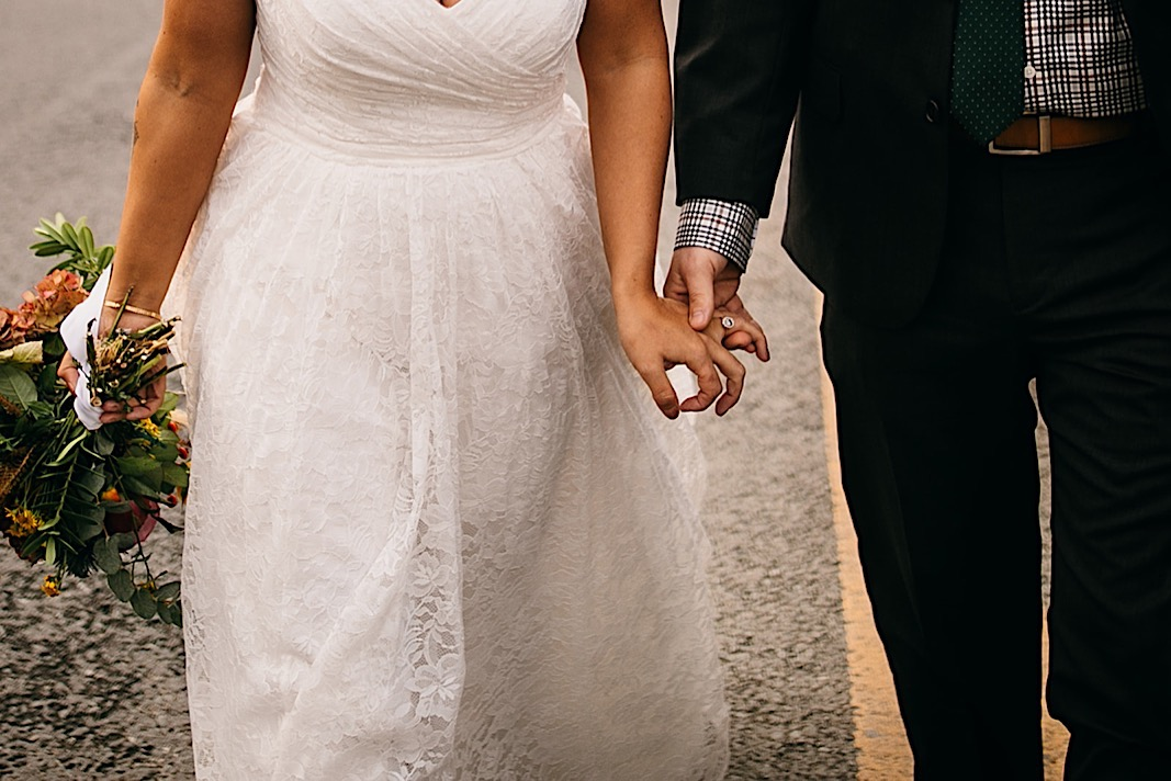 Bride and groom hold hands and smile at each other as they walk down the street at the Moher Cliffs