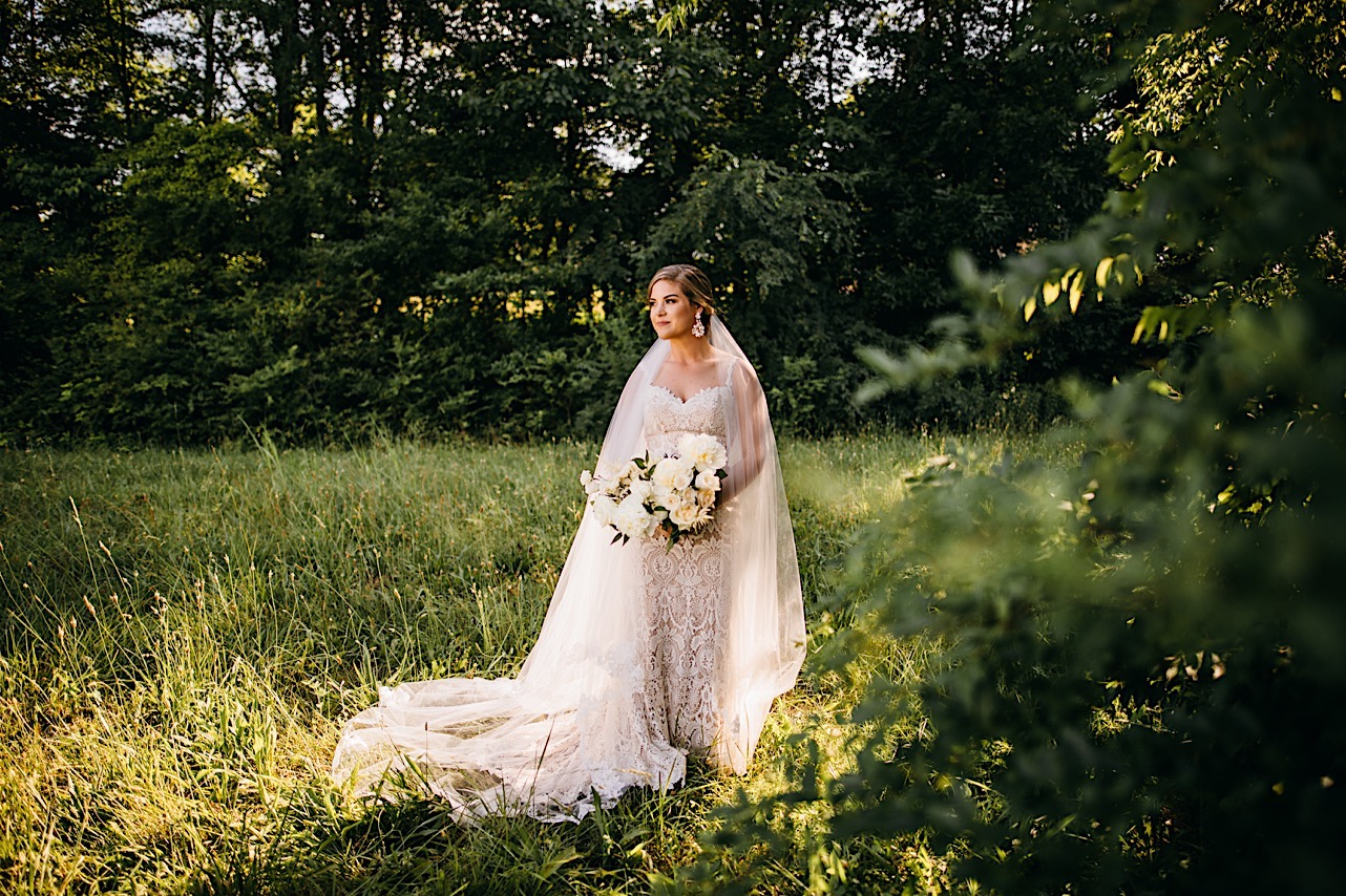 bride in lacy wedding gown and veil holding a large bouquet of white flowers stands in a grassy field surrounded by trees