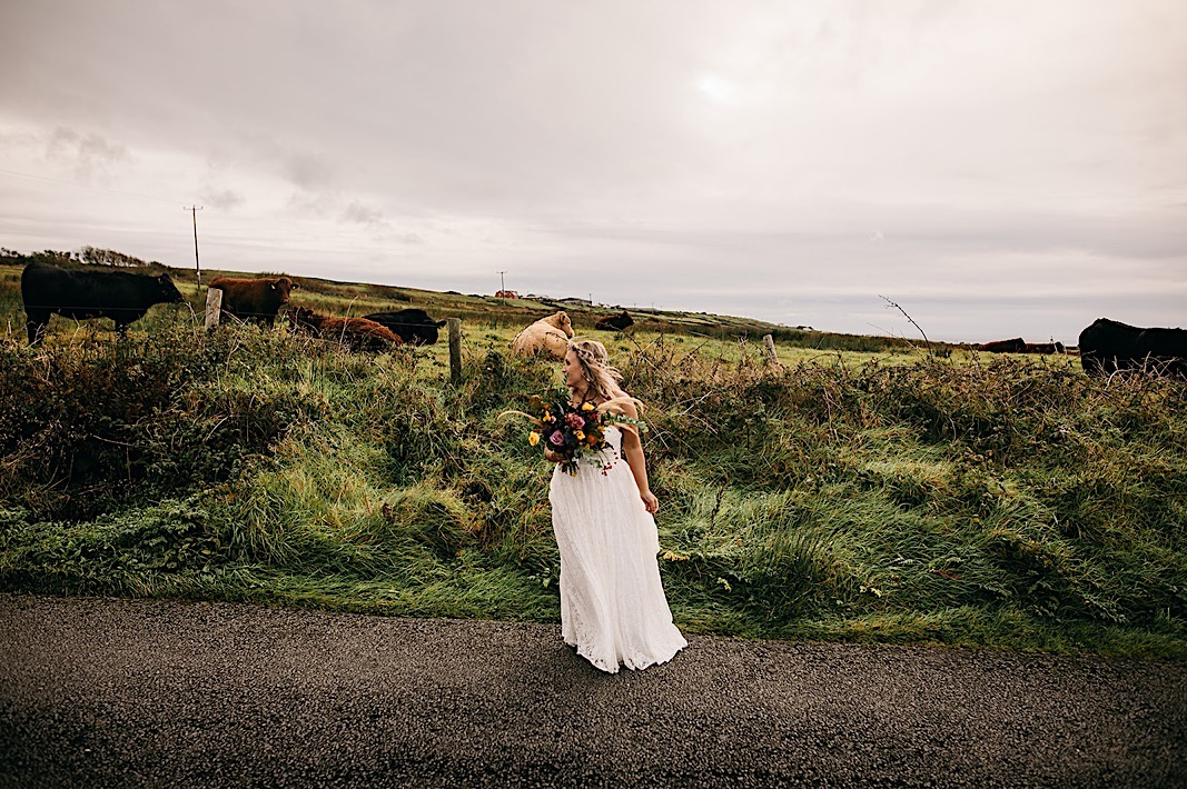 Bride holds her bouquet and smiles during her engagement photos at the Moher Cliffs