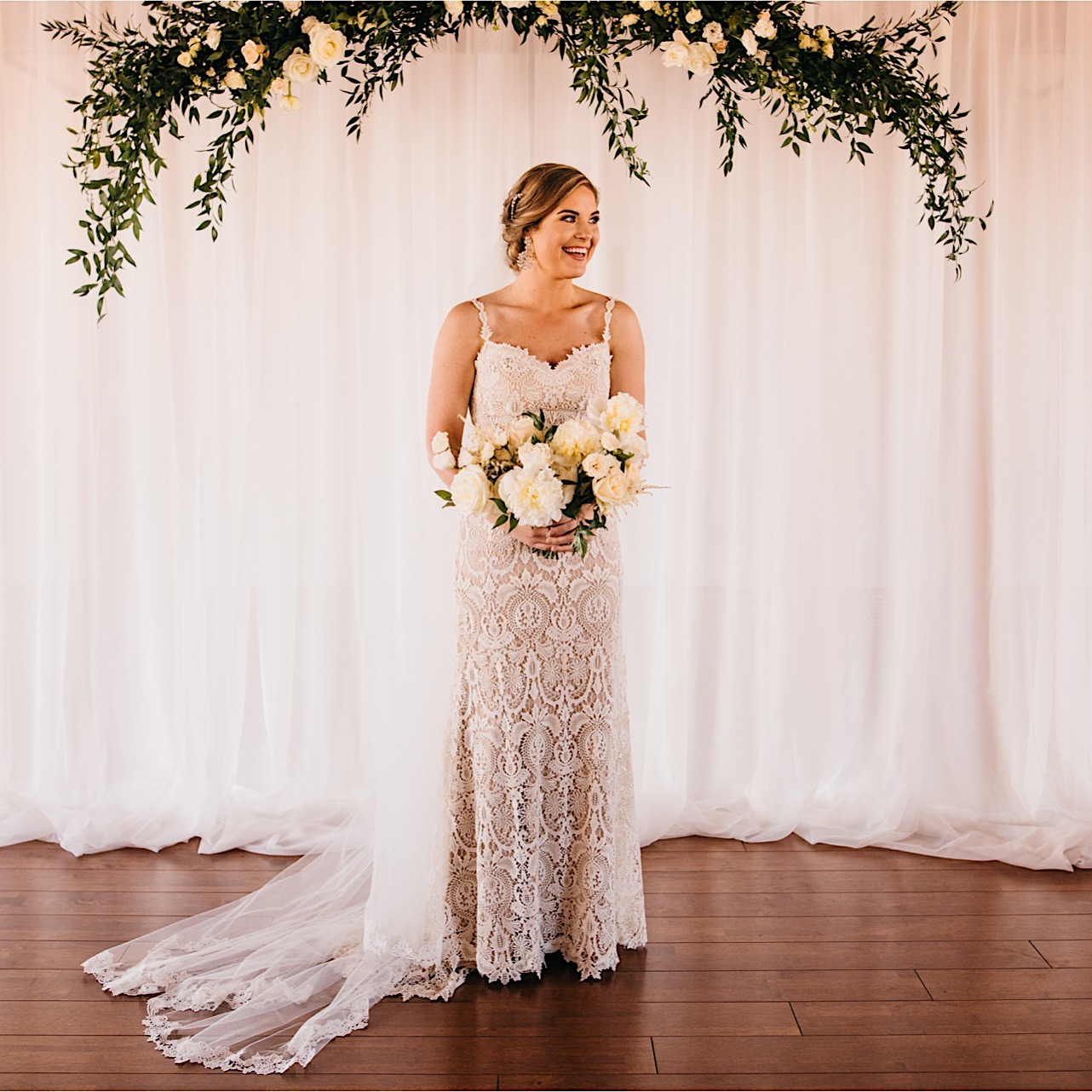 bride in lace wedding gown holding large, white Petaline bouquet beneath wedding arch made of greenery and white blooms