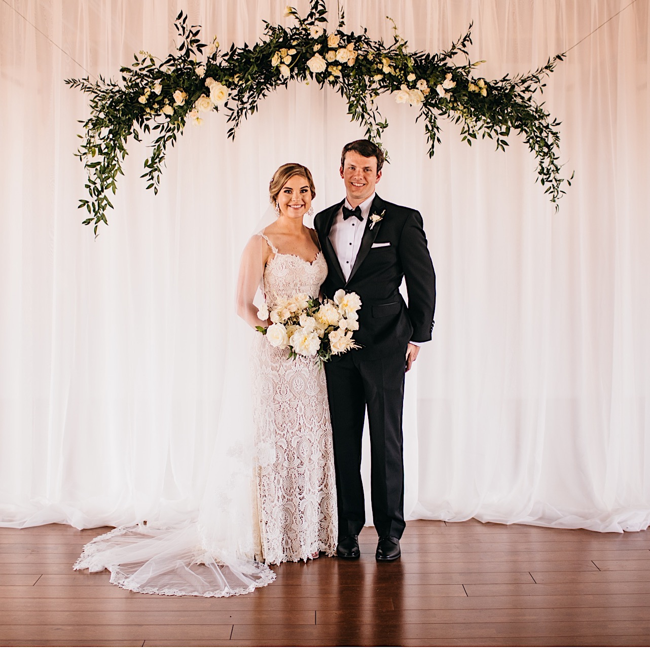 bride and groom stand in front of a tall, white curtain beneath a wedding arch made of greenery and white blooms