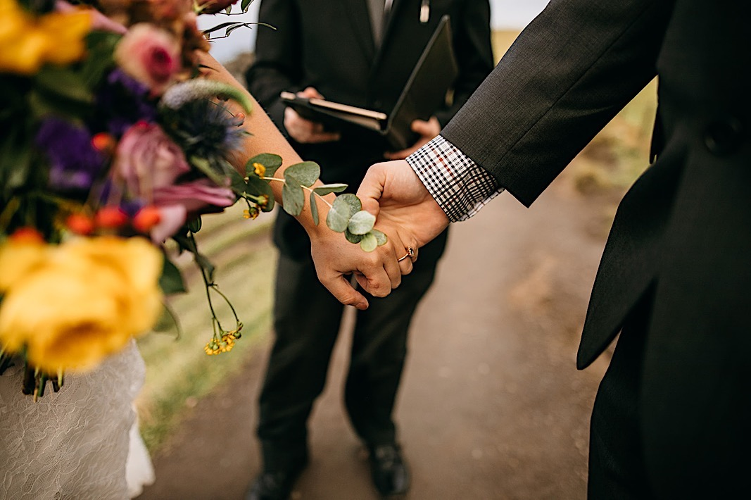 Close up of the groom holding the brides hand at the Moher Cliffs