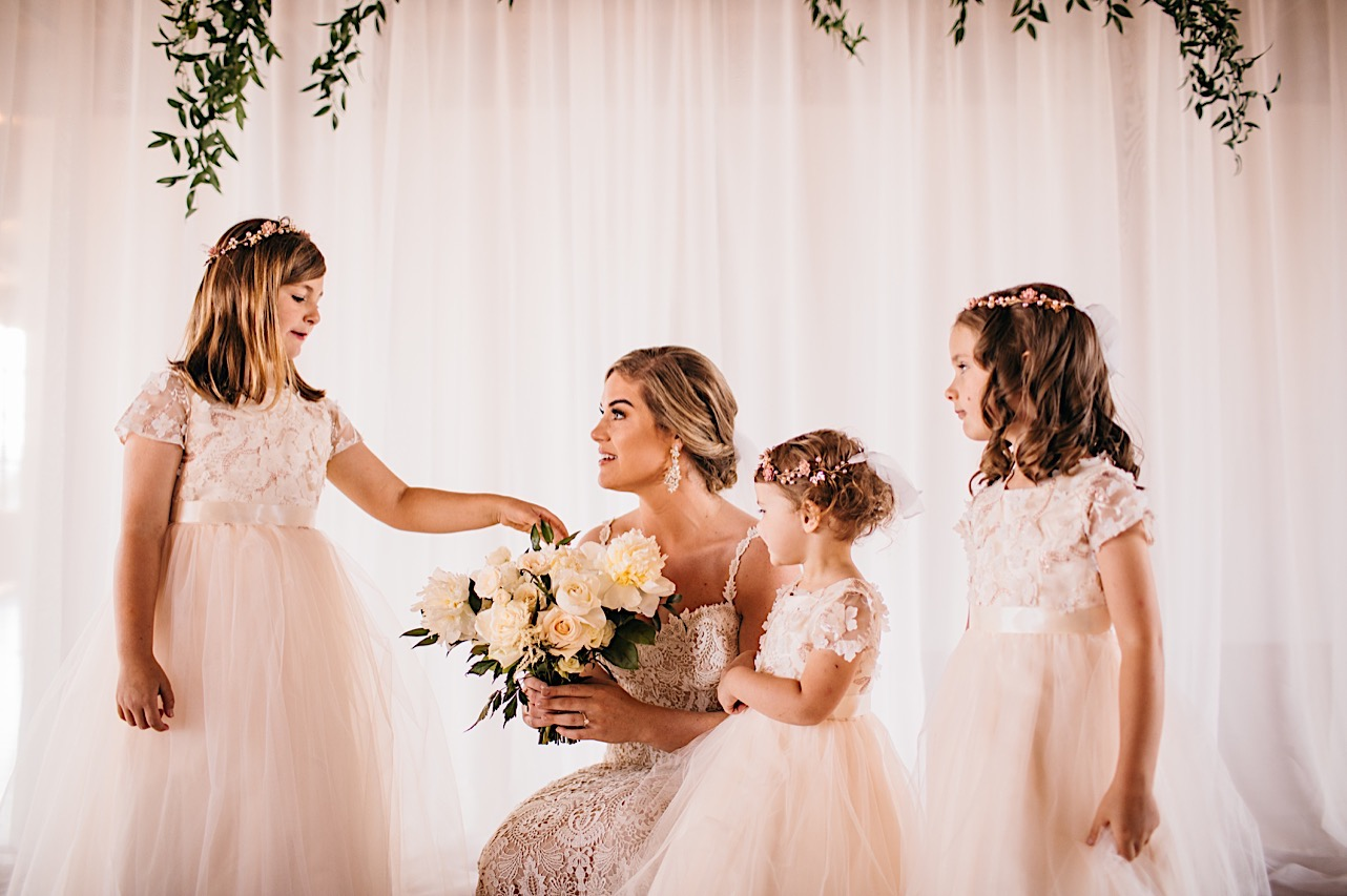 bride crouches to show her white Petaline bouquet to three flower girls in white dresses and flower crowns