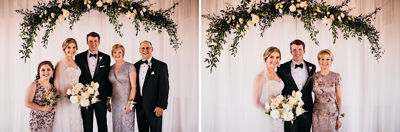 bride and groom pose with family members beneath a wedding arch made from greenery and white blooms