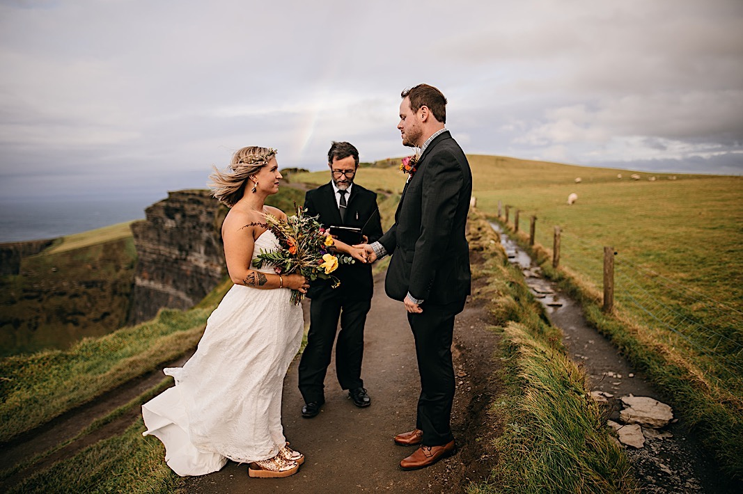 Bride and groom stand in front of an officiant on the cliffside and smile at each other during their engagement photos at the Moher Cliffs