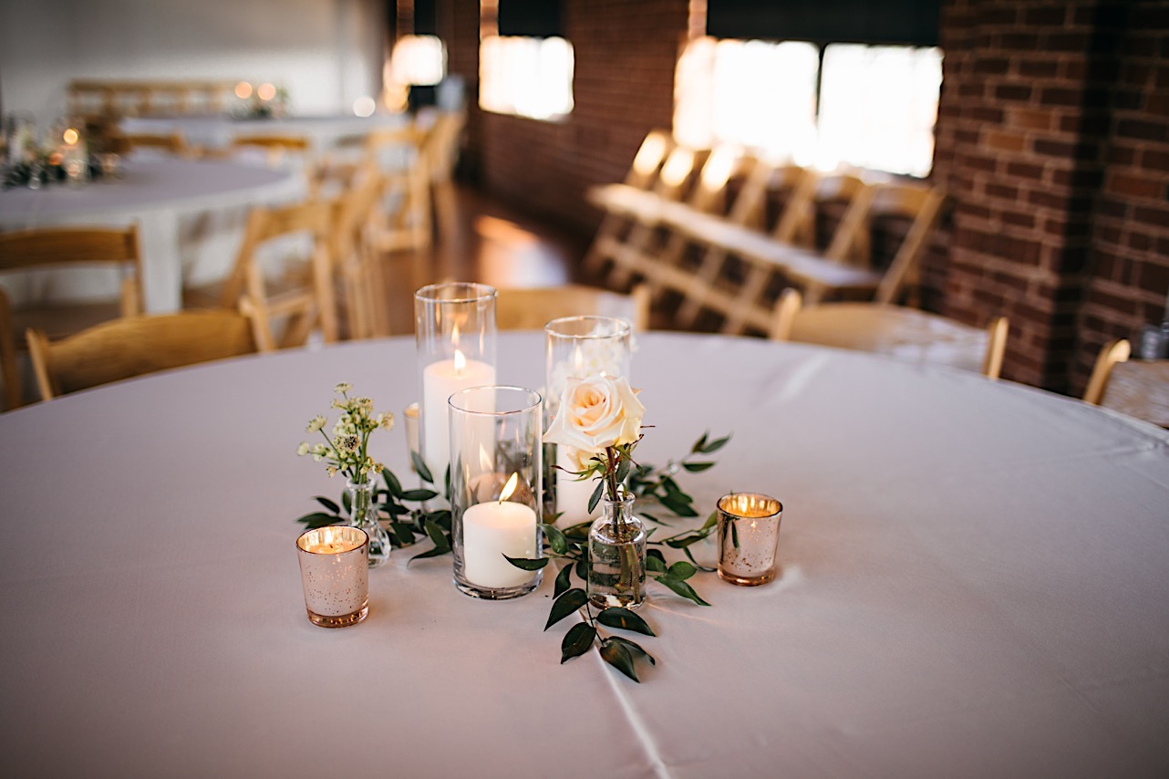 simple centerpieces of candles, greenery, and white bloom sits at the center of a round table at The Turnbull