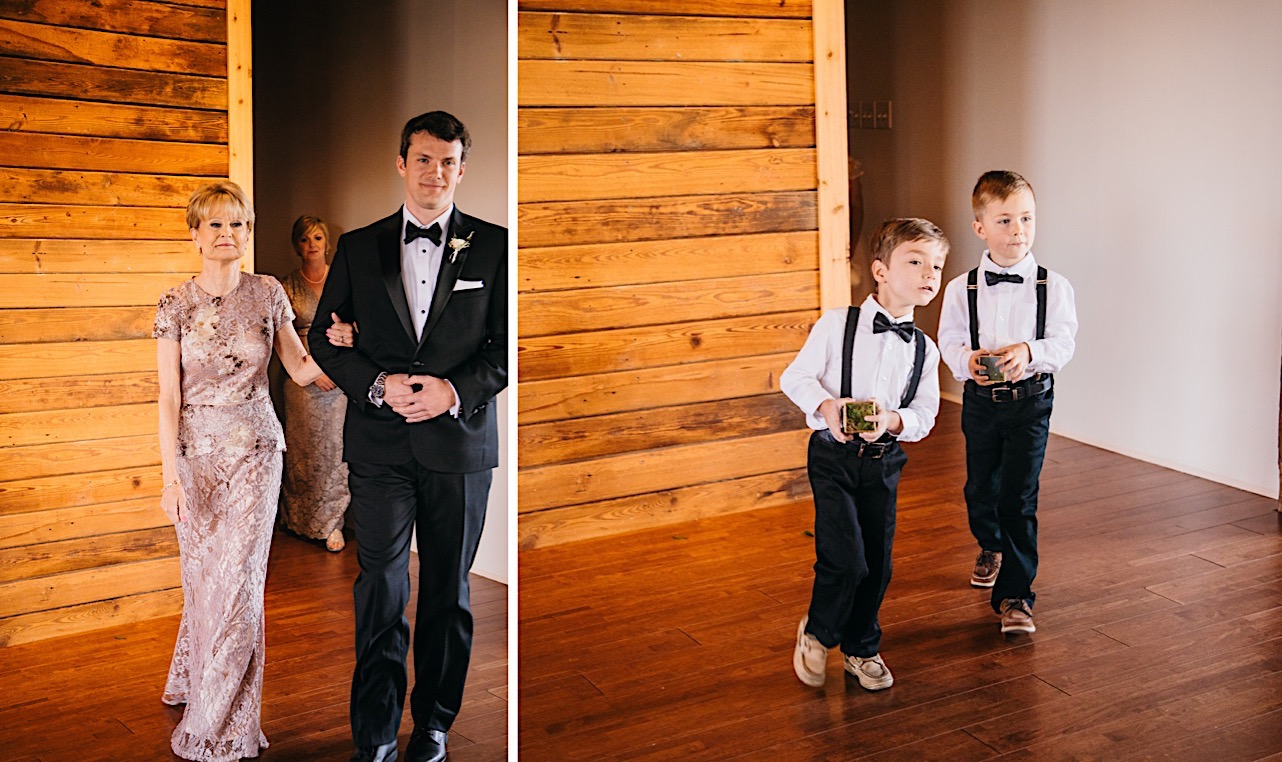 two small boys wear dark pants, bowties, and suspenders and carry small glass boxes with rings in them