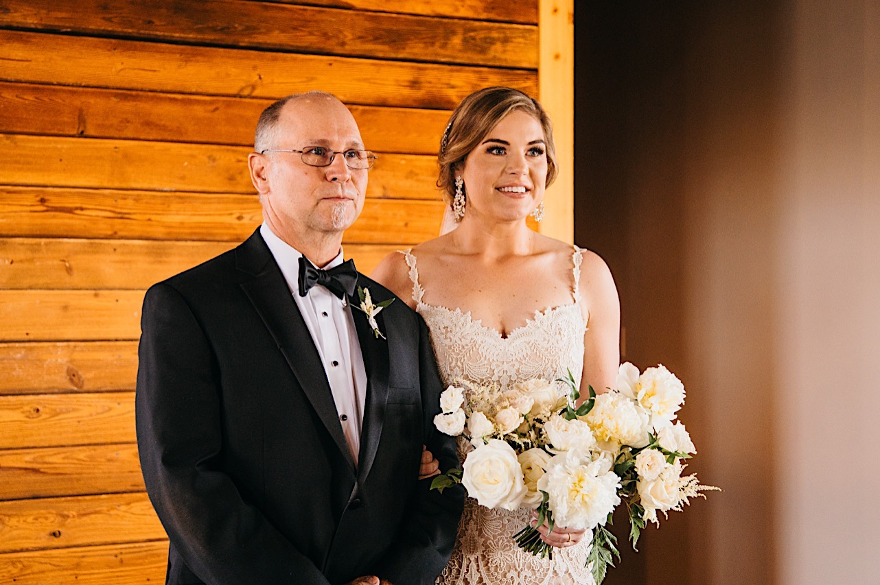 bride stands with her father in front of a shiplap wood wall. she carries a large bouquet of white flowers