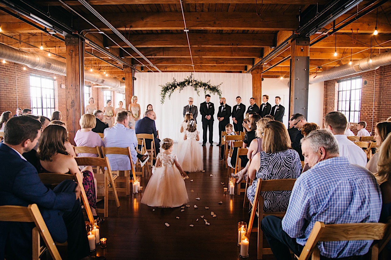 flower girls drop petals along wood floor aisle beneath the exposed rafters and beams of The Turnbull Building