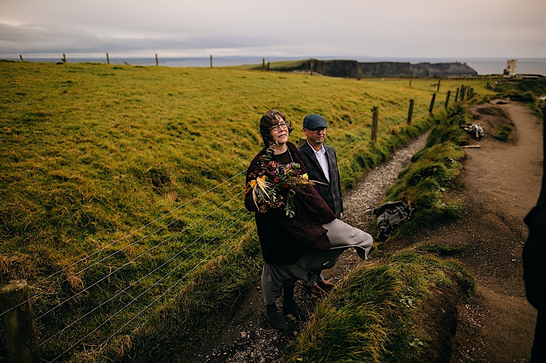 Wedding guests smile at the couple at the Moher Cliffs