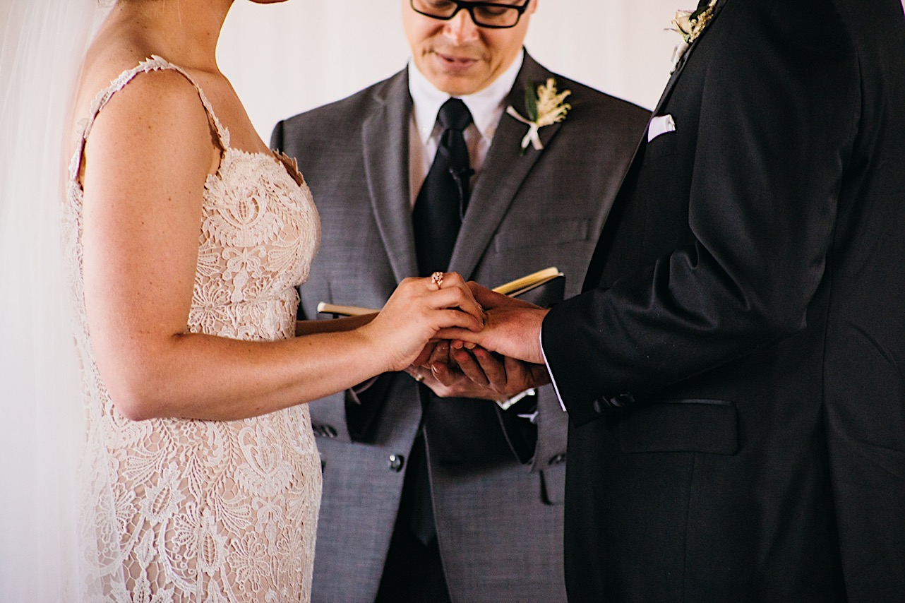 bride in lace dress slides wedding band onto groom's finger while officiant leads them in vows