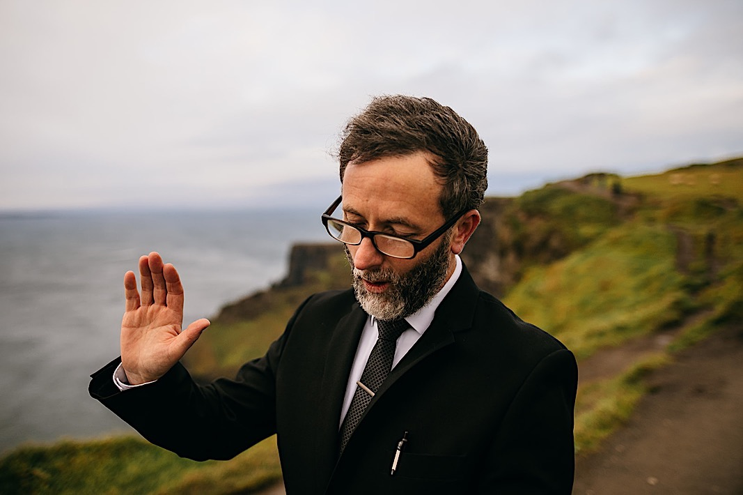 Officiant raises his hand as he reads to the couple at the Moher Cliffs