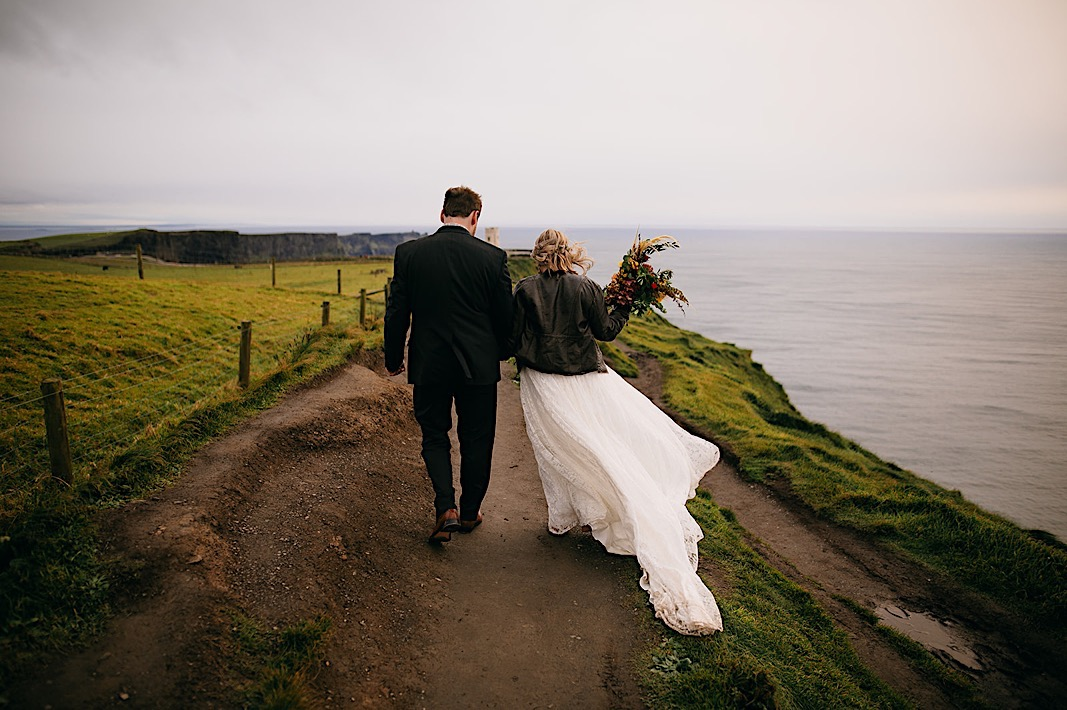 Bride and groom walk hand in hand down the cliff side of the Moher Cliffs